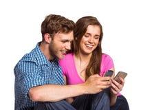 Pares alegres con los teléfonos móviles Foto de archivo