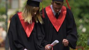 Pares alegres de graduados que dançam perto da universidade e que relaxam, estudantes engraçados video estoque
