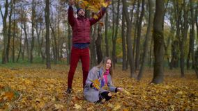 Pares alegres despreocupados que se relajan en parque del otoño metrajes