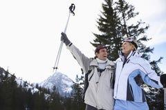 Pares alegres do esqui na roupa morna com esquis Fotografia de Stock Royalty Free