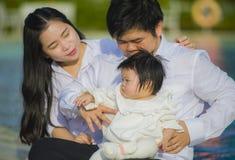 Pares alegres e doces da esposa e do marido com o bebê e o homem da terra arrendada da mãe que jogam com pouca filha no coreano a fotografia de stock