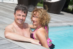 Pares alegres e encantadores que têm o divertimento na piscina Imagem de Stock