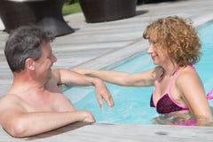 Pares alegres e encantadores que têm o divertimento na piscina Foto de Stock Royalty Free