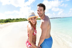 Pares alegres en la playa en las zonas tropicales Imagen de archivo libre de regalías
