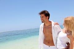 Pares alegres en una playa paradisíaca Imagen de archivo