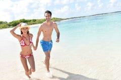 Pares alegres felices que corren en la playa Imagen de archivo