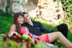 Pares alegres felizes que encontram-se na grama verde e nos risos Fotografia de Stock Royalty Free