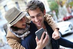 Pares alegres felizes que obtêm uma boa notícia no smartphone Imagem de Stock