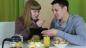 Pares alegres jovenes en el amor que mira la tableta almacen de metraje de vídeo
