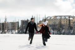 Pares alegres jovenes que disfrutan de la estación del invierno Imagen de archivo libre de regalías