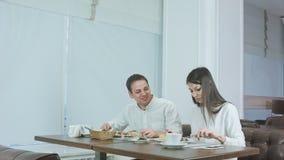Pares alegres jovenes que disfrutan del almuerzo de negocios en el restaurante metrajes