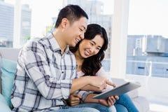 Pares alegres jovenes que miran la tableta digital Foto de archivo