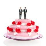Pares alegres misturados sobre o bolo de casamento Imagens de Stock