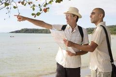 Pares alegres nas férias que apontam no destino imagens de stock royalty free