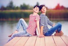 Pares alegres no amor no banco de rio foto de stock royalty free