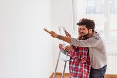 Pares alegres novos que escolhem a cor para a casa de pintura foto de stock royalty free