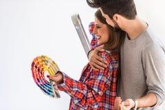 Pares alegres novos que escolhem a cor para a casa de pintura imagens de stock