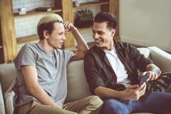 Pares alegres novos que sentam-se em um sofá e em um sorriso imagens de stock royalty free