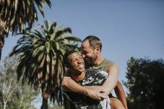 Pares alegres que abraçam no parque fotografia de stock royalty free
