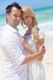 Pares alegres que abrazan y que presentan en la playa en un día soleado Foto de archivo