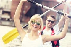 Pares alegres que canoeing no rio Imagens de Stock