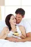 Pares alegres que comem as panquecas que encontram-se em sua cama fotografia de stock royalty free