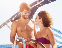 Pares alegres que conducen el velero Foto de archivo libre de regalías