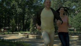 Pares alegres que correm no parque vídeos de arquivo