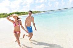 Pares alegres que corren en la playa Fotos de archivo libres de regalías