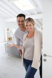 Pares alegres que dão boas-vindas a convidados a sua casa nova Fotos de Stock Royalty Free