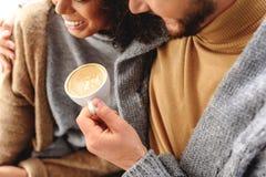 Pares alegres que gozan de un latte caliente Fotografía de archivo