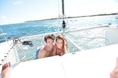 Pares alegres que gozan en el catamarán fotografía de archivo