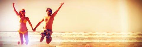 Pares alegres que guardam as mãos ao saltar na praia imagens de stock royalty free