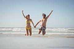 Pares alegres que guardam as mãos ao saltar na praia foto de stock royalty free