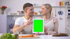 Pares alegres que guardam a tabuleta com tela verde, molde em linha da compra de alimento vídeos de arquivo