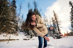 Pares alegres que juegan al aire libre en invierno Foto de archivo