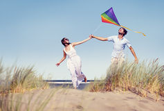 Pares alegres que juegan la cometa por la playa fotos de archivo libres de regalías