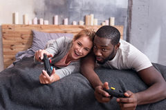 Pares alegres que juegan a los videojuegos en cama Imagen de archivo libre de regalías