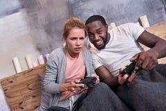 Pares alegres que juegan videojuegos juntos Imágenes de archivo libres de regalías