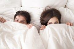 Pares alegres que mienten en cama debajo de la cubierta que mira la cámara Fotos de archivo libres de regalías