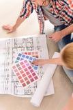Pares alegres que miran plan de la casa de la construcción fotos de archivo