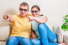 Pares alegres que olham um filme engraçado Fotografia de Stock Royalty Free