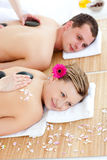 Pares alegres que reciben masaje posterior con las piedras calientes Fotos de archivo