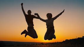 Pares alegres que saltan en la puesta del sol almacen de video
