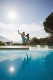 Pares alegres que saltan en piscina Fotografía de archivo
