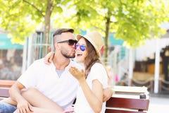 Pares alegres que se besan en un banco fotografía de archivo libre de regalías