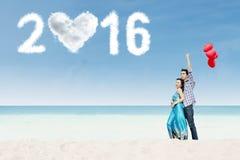 Pares alegres que se colocan en la playa con los números 2016 Fotos de archivo libres de regalías