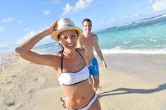 Pares alegres que se divierten en la playa Foto de archivo