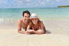Pares alegres que se relajan en la playa arenosa blanca Imagen de archivo