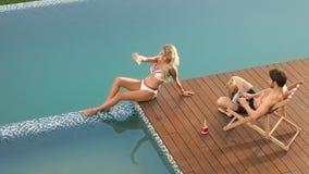 Pares alegres que se relajan en poolside Mujer atractiva que toma la foto del selfie cerca de piscina almacen de metraje de vídeo